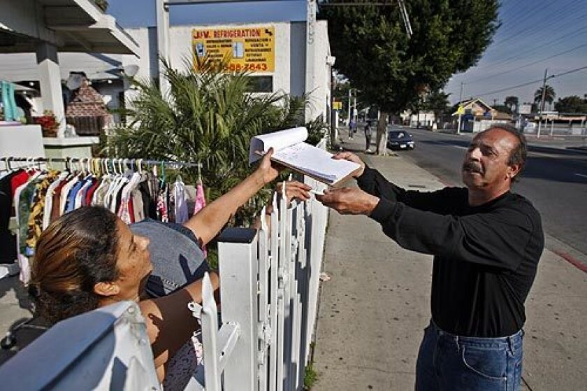 Eddie Caire, a civic activist and former labor organizer from the Florence-Firestone neighborhood just north of Watts, collects a signature from Beda Padilla in favor of bringing a Wal-Mart to the area.