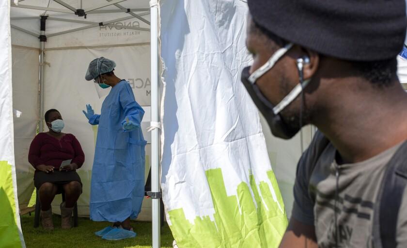 FILE — In this May 8, 2020, file photo a man looks into a tent as a health worker in protective gear collects a sample for COVID-19 testing in Diepsloot, Johannesburg, South Africa. South Africa's reported coronavirus are surging. Its hospitals are now bracing for an onslaught of patients, setting up temporary wards and hoping advances in treatment will help the country's health facilities from becoming overwhelmed. (AP Photo/Themba Hadebe, File)