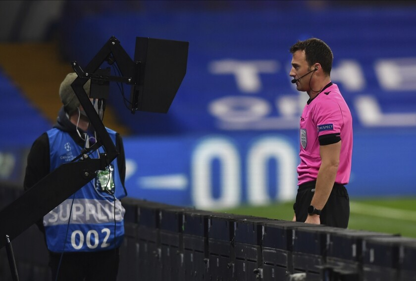 A referee watches an incident on the VAR screen before awarding a penalty to Chelsea during the Champions League Group E soccer match between Chelsea and Rennes at Stamford Bridge, London, England, Wednesday Nov. 4, 2020. (Ben Stansall/Pool via AP)