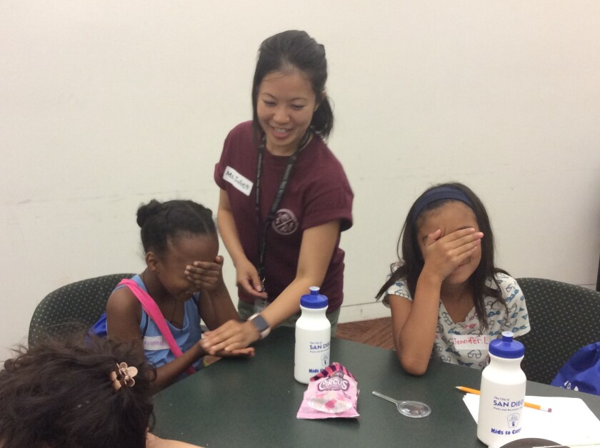Program instructor Juliet Huang teaches Savannah Ghebrezabher, 9, and Jennifer Lopez, 10, about insect defenses at Valencia Park/Malcolm X Branch Library.