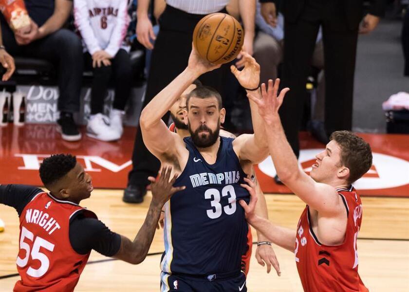 El español Marc Gasol (c) de Memphis Grizzlies pasa el balón ante Delon Wright (i) y Jakob Poeltl (d) de Toronto Raptors hoy, domingo 4 de febrero de 2018, durante un juego de la NBA entre Memphis Grizzlies y Toronto Raptors en Toronto (Canadá). EFE
