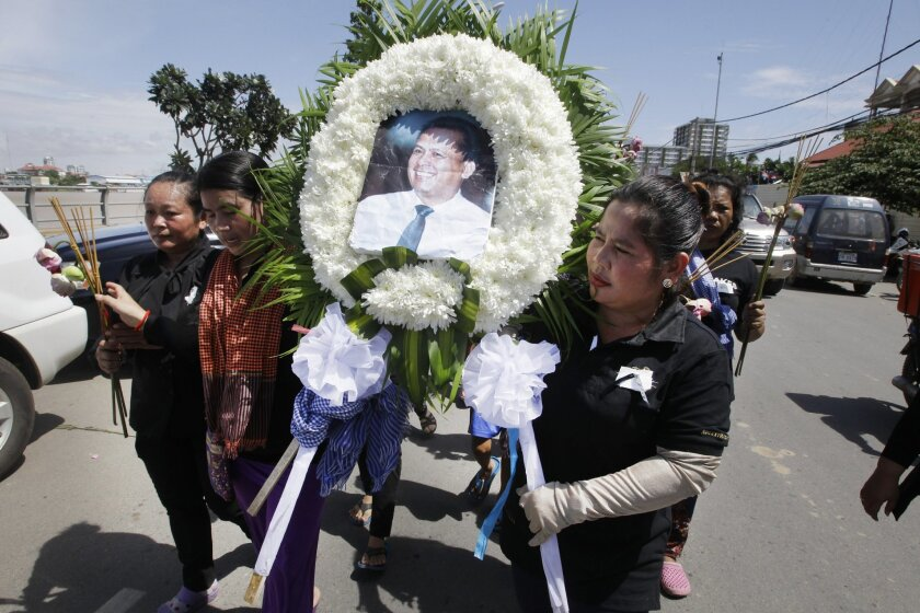 FILE - In this July 11, 2016 file photo, Cambodian community activists carry a wreath during the funeral procession of government critic Kem Ley, pictured, in Phnom Penh, Cambodia.  Oeut Ang, the man who allegedly shot dead Kem Ley over what he claimed was a money dispute is too poor to have loaned