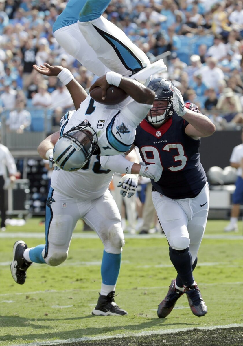 Carolina Panthers' Cam Newton (1) dives over Houston Texans' Jared Crick (93) for a touchdown during the second half of an NFL football game in Charlotte, N.C., Sunday, Sept. 20, 2015. (AP Photo/Chuck Burton)