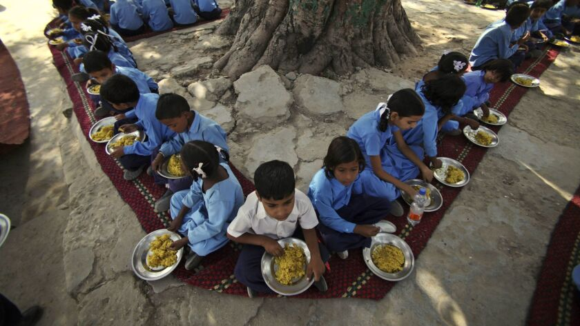 Indian schoolchildren eat a free midday meal, provided on all working days at a government school on