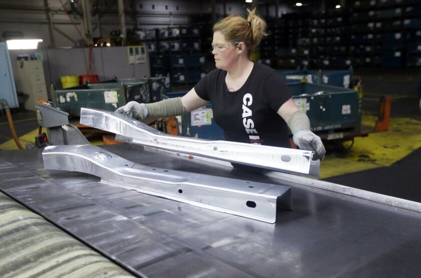 United Auto Workers line worker Crystal McIntyre unloads parts from a stamping machine at the General Motors Pontiac Metal Center in Pontiac, Mich., Thursday, April 30, 2015. The automaker plans to spend $5.4 billion to improve its U.S. factories during the next three years, creating about 650 new jobs. (AP Photo/Carlos Osorio)