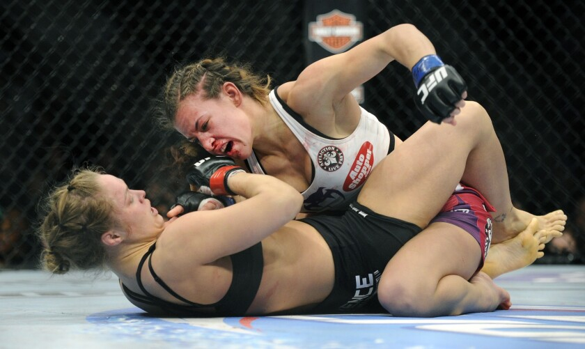 Miesha Tate, top, punches Ronda Rousey during their bantamweight title fight at UFC 168 in Las Vegas in 2013.