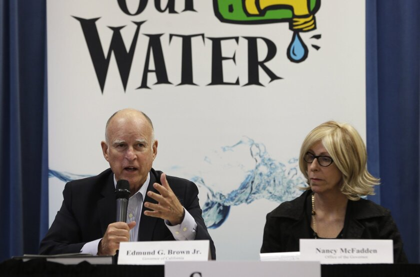 Gov. Jerry Brown, with Executive Secretary Nancy McFadden, talks to reporters at the end of a meeting on the drought last week.