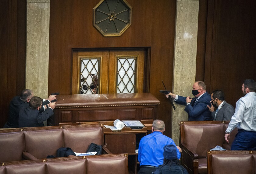 Security officers point guns at House chamber door as a mob storms the Capitol Jan. 6.