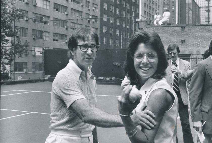 Bobby Riggs grabs Billie Jean King's upper arm on the tennis court in a 1973 black-and-white photo.