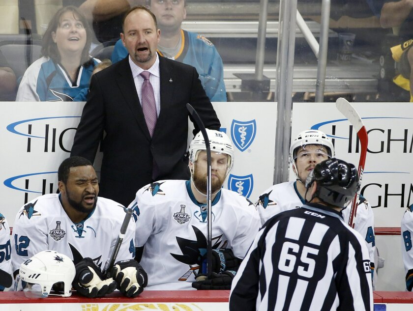 San Jose Sharks coach Peter DeBoer speaks to linesman Pierre Racicot (65) during the first period against the Pittsburgh Penguins in Game 2 of the NHL hockey Stanley Cup Finals on Wednesday, June 1, 2016, in Pittsburgh. (AP Photo/Gene J. Puskar)