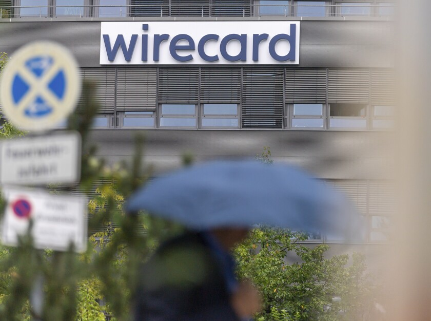 A person walk in front of a building with the logo of the insolvent company Wirecard in Aschheim near Munich, Germany, Tuesday, Sept. 1, 2020. German opposition parties plan to force the launch of a parliamentary inquiry into the downfall of bankrupt payment company Wirecard. (Peter Kneffel/dpa via AP)