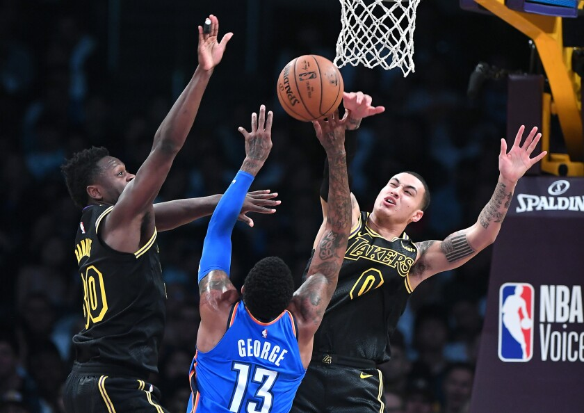 Lakers forward Kyle Kuzma, right, blocks a shot from Thunder forward Paul George as Julius Randle helps on defense during a game Thursday at Staples Center.