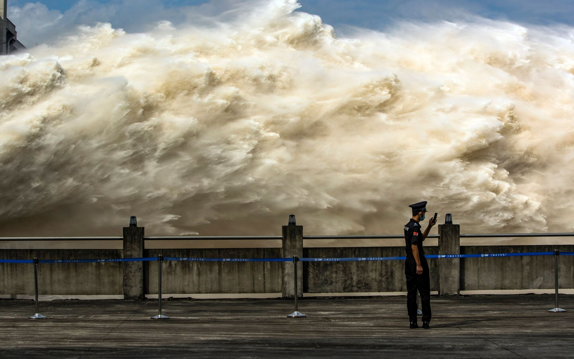 A security guard looks at his smartphone while water is released from Three Gorges Dam in central China.