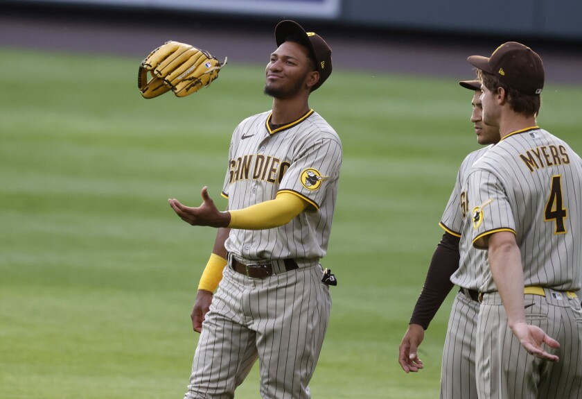 Padres' Edward Olivares, left, tosses his glove while chatting with center fielder Trent Grisham, center, and Wil Myers.