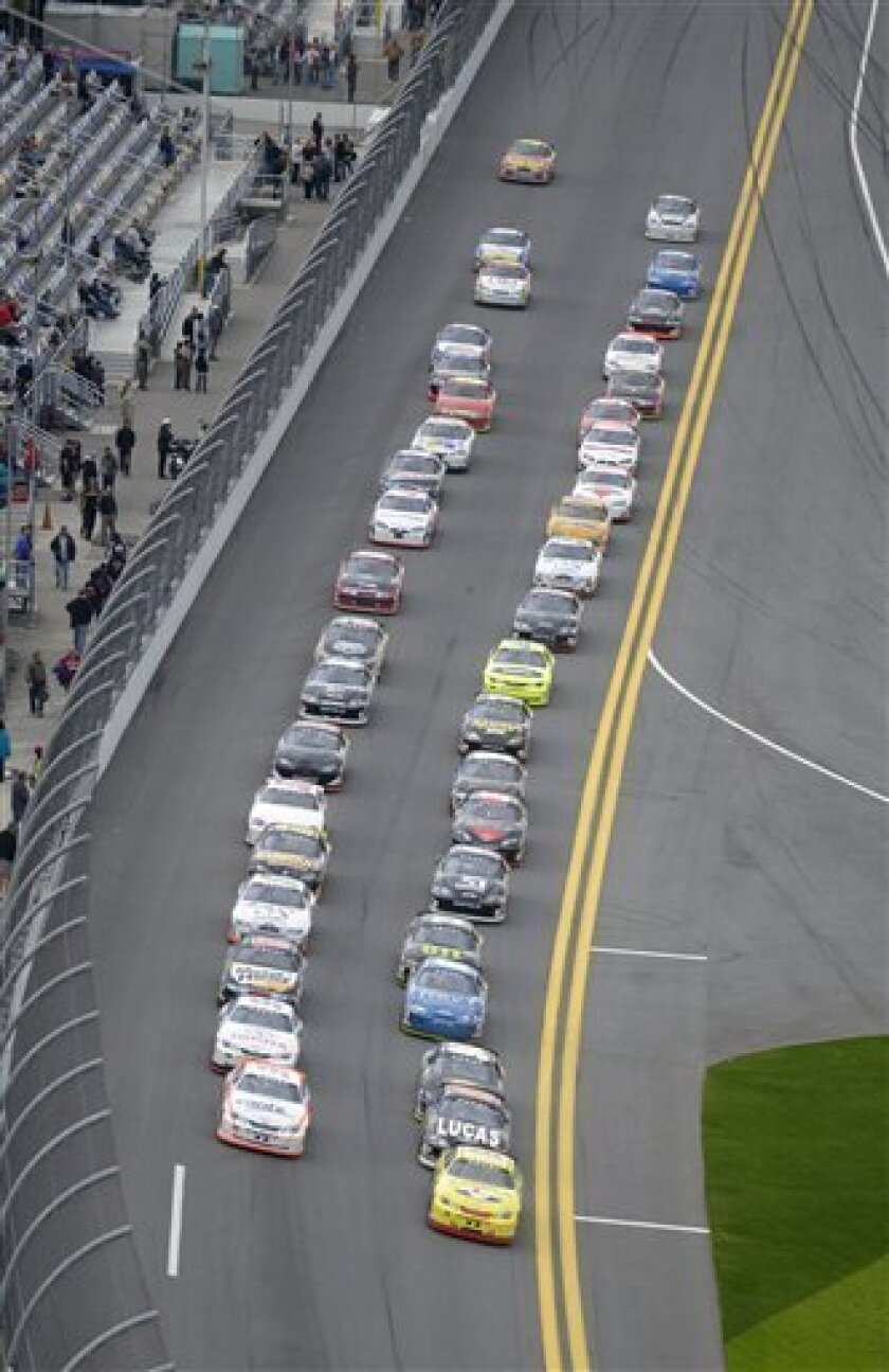 Racers pass the front grandstands of the Daytona International Speedway for the start of the ARCA Series Lucas Oil 200 auto race in Daytona Beach, Fla., Saturday, Feb. 16, 2013.(AP Photo/Phelan M. Ebenhack)