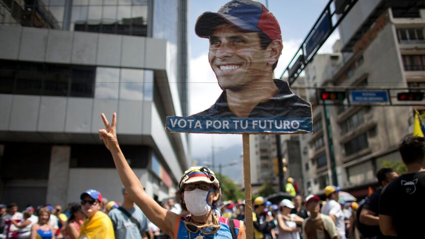 A woman shows her support for Venezuelan opposition leader Henrique Capriles as people gather for a demonstration against President Nicolas Maduro in Caracas, Venezuela, on April 8.