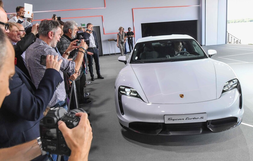 The Porsche Taycan electric car is presented during the a world premiere on Sept. 4, 2019 in a hall of the airfield in Neuhardenberg, Germany. The first pure electric model is presented at the same time on three continents and will be delivered at the end of the year, starting in the United States.