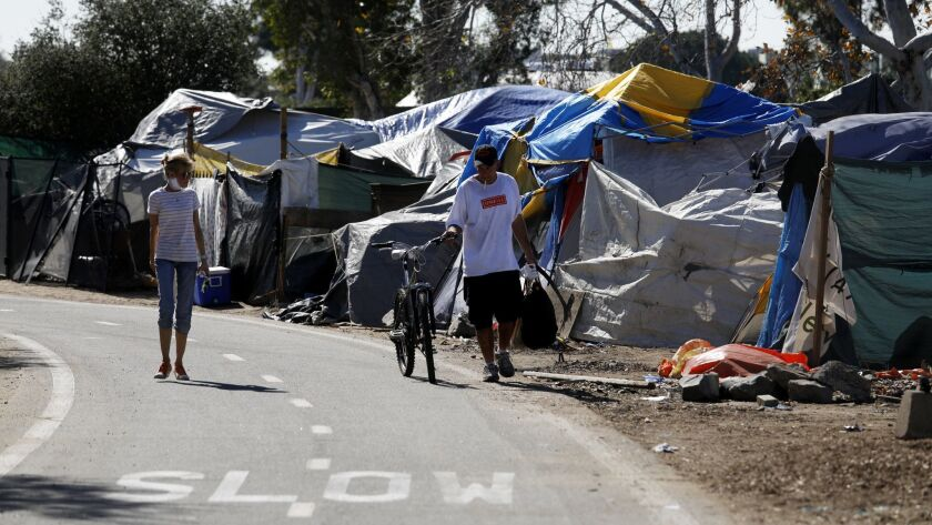 People walk past tents at a homeless encampment along the Santa Ana River trail in February in Anaheim. Orange County supervisors put forth a proposal Monday to move homeless people to temporary shelters in Irvine, Huntington Beach and Laguna Niguel.