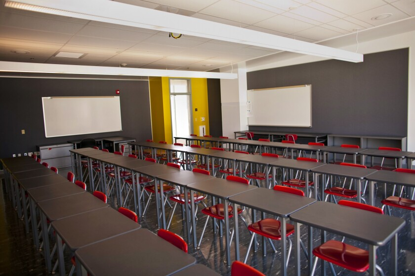 An empty classroom has desks placed close together before the coronavirus pandemic.