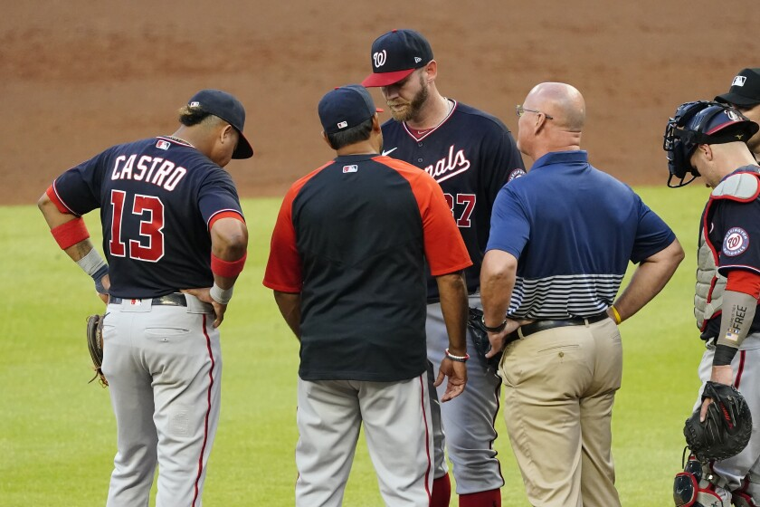 Washington Nationals starting pitcher Stephen Strasburg, center, talks with manager Dave Martinez and a member of the team's medical staff before exiting a baseball game in then second inning against Atlanta Braves Tuesday, June 1, 2021, in Atlanta. (AP Photo/John Bazemore)