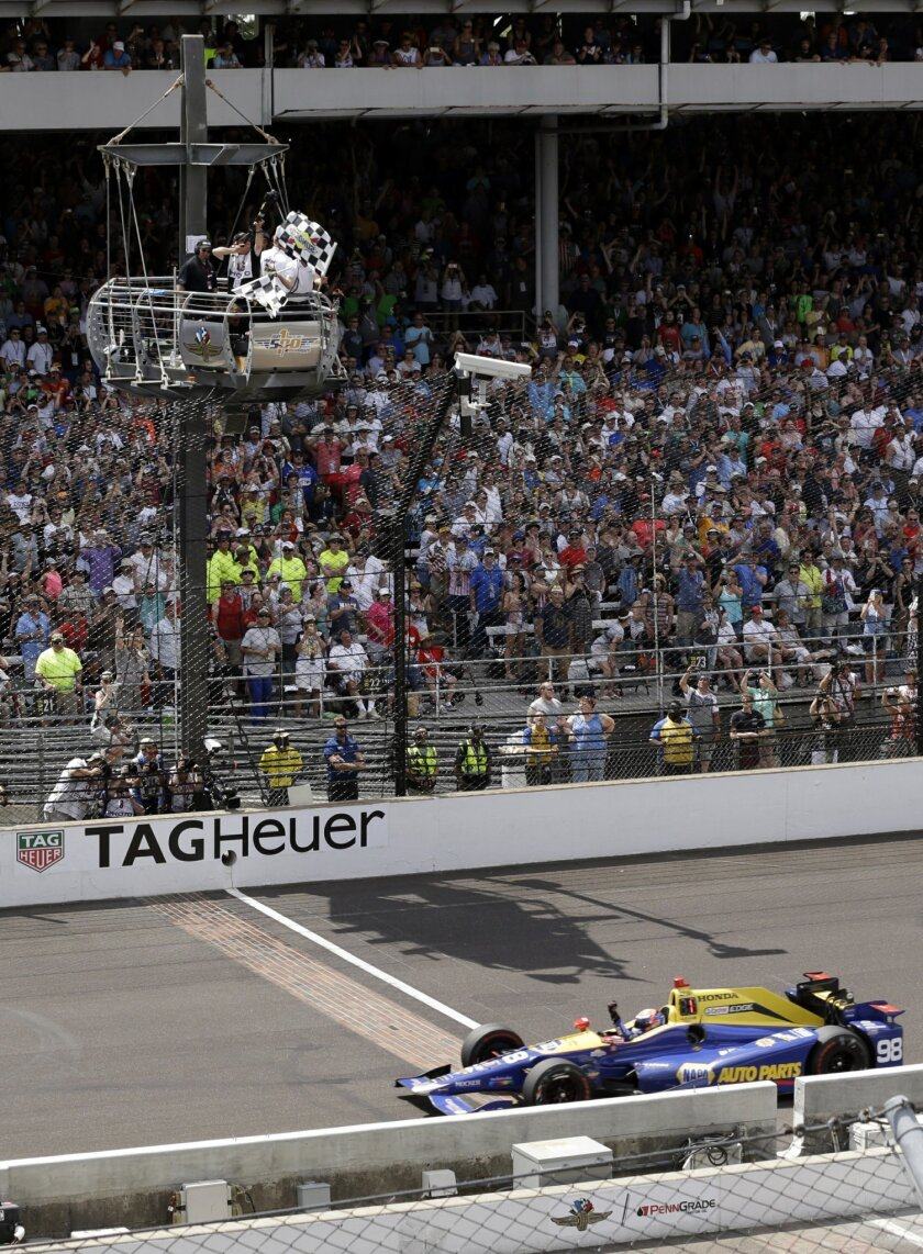 Alexander Rossi takes the checkers flags as he crosses the finish line to win the 100th running of the Indianapolis 500 auto race at Indianapolis Motor Speedway in Indianapolis, Sunday, May 29, 2016. (AP Photo/Dave Parker)