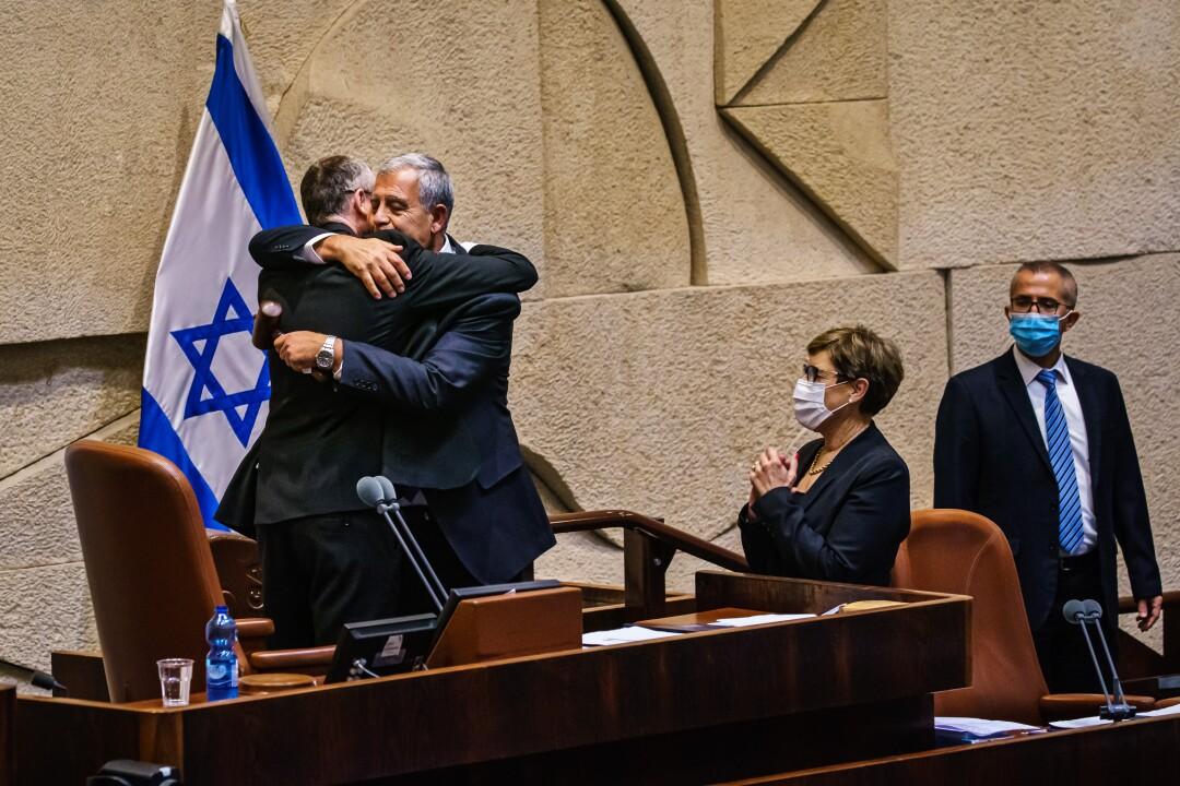 Israeli politicians hug at desk.