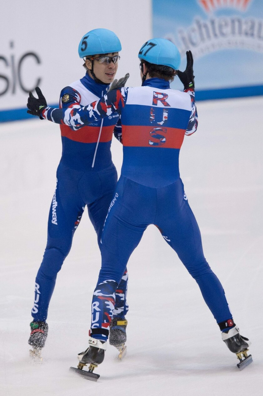Russia's Semen Elistratov, left,  and Dmitry Migunov react after crossing the finish line during the men's 5,000 m relay final at the ISU Short track World Cup event in Dresden, Germany, Sunady feb. 7, 2016.  Russia won the relay competition. (Sebastian Kahnert/dpa via AP)
