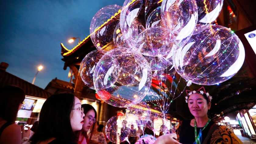 A woman sells balloons in Hong Ya Dong, or Red Cliff Cave, in Chongqing, China. Chongqing, in the southwest, is one of China's top tourism cities.