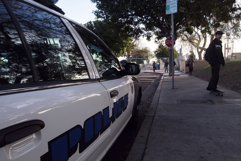 A skateboarder passes an LAUSD School Police car on his way to class Wednesday as students return to San Pedro High School.