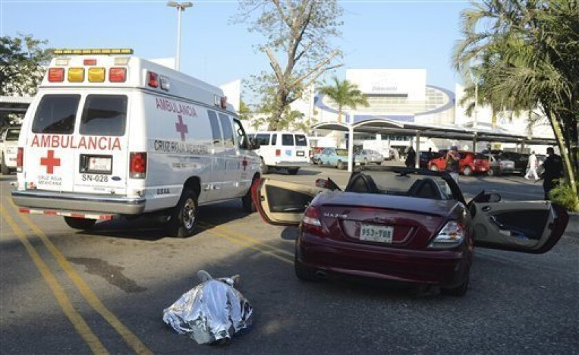 The body of a man identified as a Belgian citizen lies in the ground next to his car after he was shot dead by unknown assailants as he was leaving a supermarket in the Pacific resort city of Acapulco, Mexico, Saturday Feb. 23, 2013. The incident occurred a very short distance from the Fairmont Acapulco Princess where the Mexico Tennis Open is slated to begin next Monday. (AP Photo/Bernandino Hernandez)
