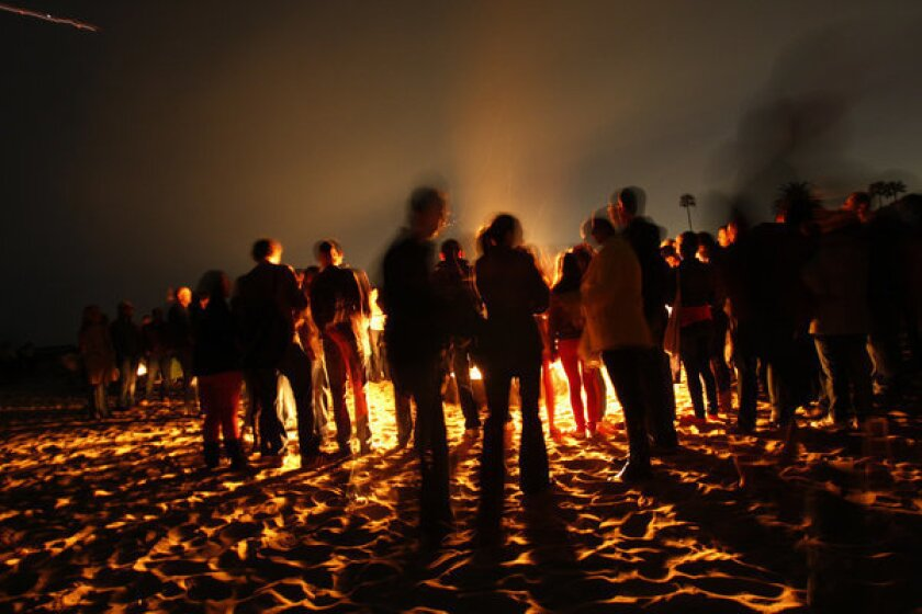 People gather around a bonfire at Corona del Mar State Beach. The issue of beach bonfires is being discussed by the state Coastal Commission and the South Coast Air Quality Management District.