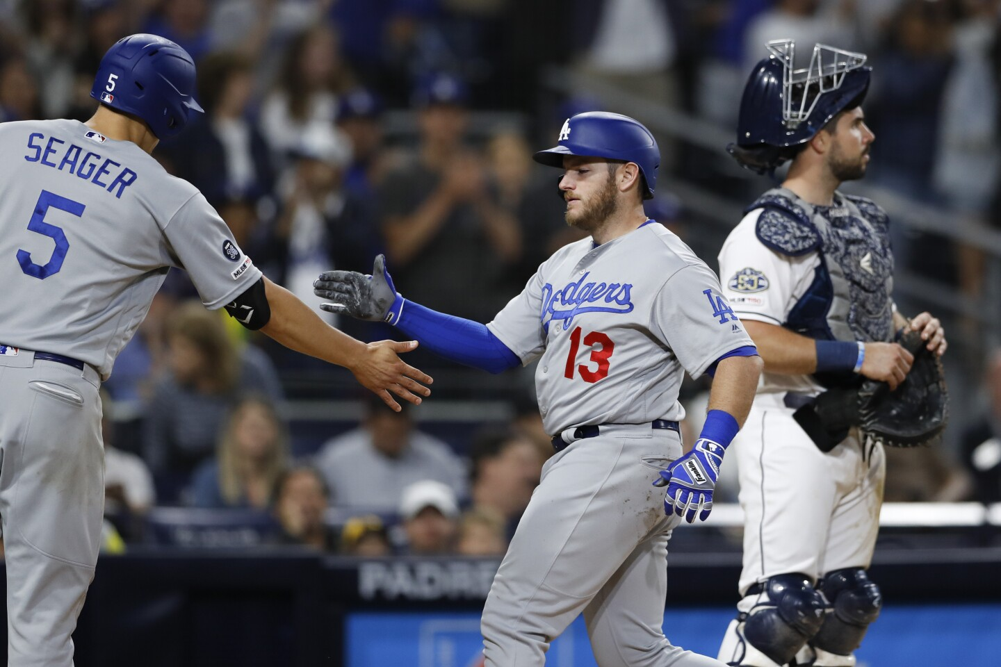 The Los Angeles Dodgers' Max Muncy is greeted by teammate Corey Seager (5) after hitting a three-run home run during the sixth inning of a baseball game against the San Diego Padres, Saturday, May 4, 2019, in San Diego. (AP Photo/Gregory Bull)