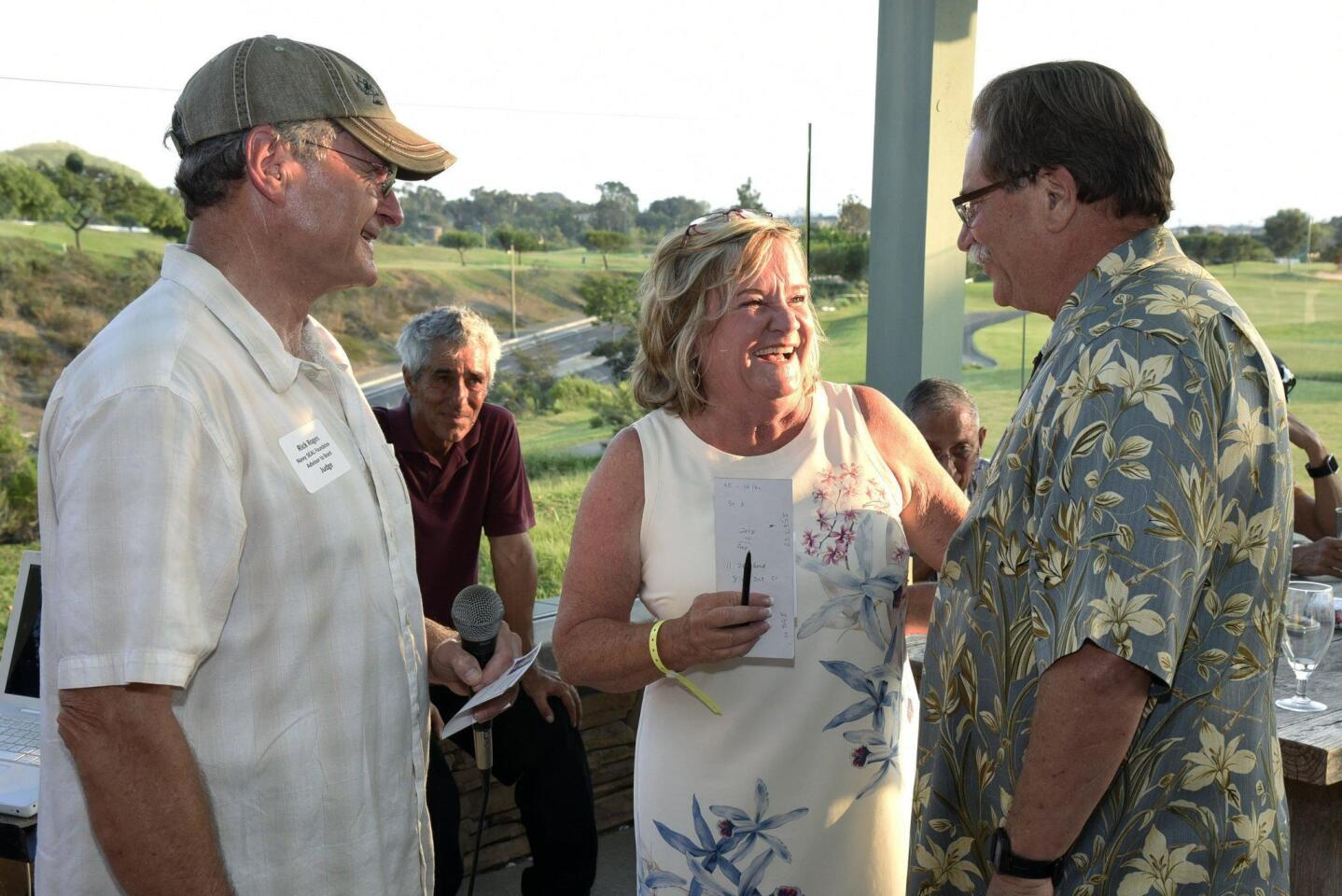 Military Board of Advisors to the Navy Seal Foundation member Rick Rogers and event chair Gretchen Mitchell present prize to 1st place golf ball drop winner Don Heiser
