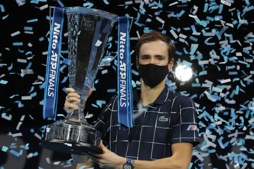 Daniil Medvedev of Russia holds up the winners trophy as confetti falls after defeating Dominic Thiem.