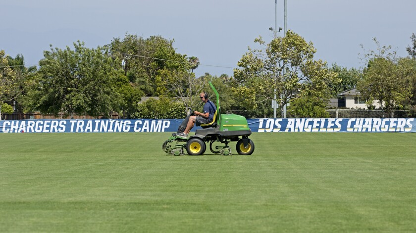 A worker trims the field where the Los Angeles Chargers hold training camp at Jack R. Hammett Sports Complex in Costa Mesa.