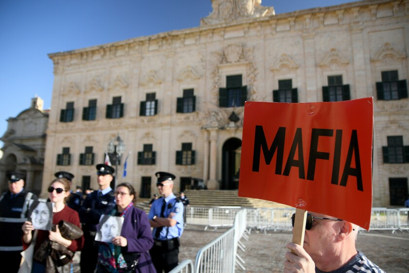 People protest outside the office of the Prime Minister at Castille, in Valletta, Malta, Tuesday, Dec. 3, 2019, as a delegation od European Union lawmakers is visiting the country after an investigation into the murder of leading investigative journalist Daphne Caruana Galizia implicated Prime Minister Joseph Muscat's chief of staff. (AP Photo/Rene Rossignaud)