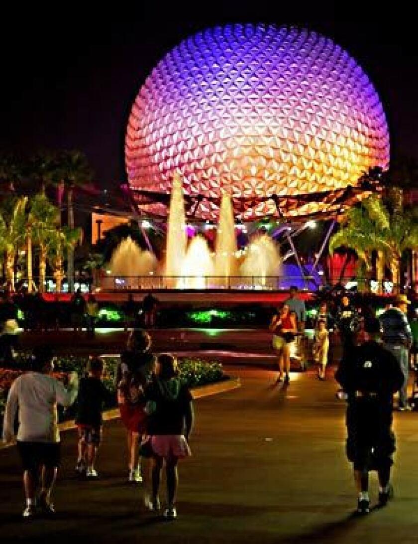 Visitors walk near Spaceship Earth at Walt Disney World's Epcot Center theme park in Orlando, Fla.