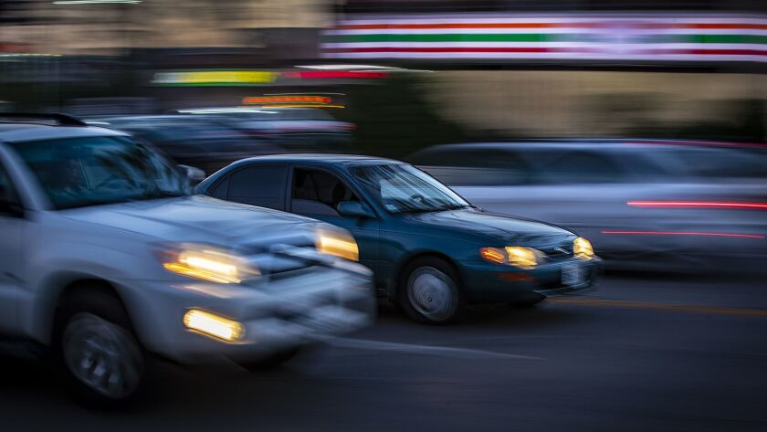 L.A. officials are considering raising speed limits on more than 100 miles of city streets in order to comply with a state law that has prevented police officers from ticketing speeders. Above, cars travel along Zelzah Avenue in the San Fernando Valley.
