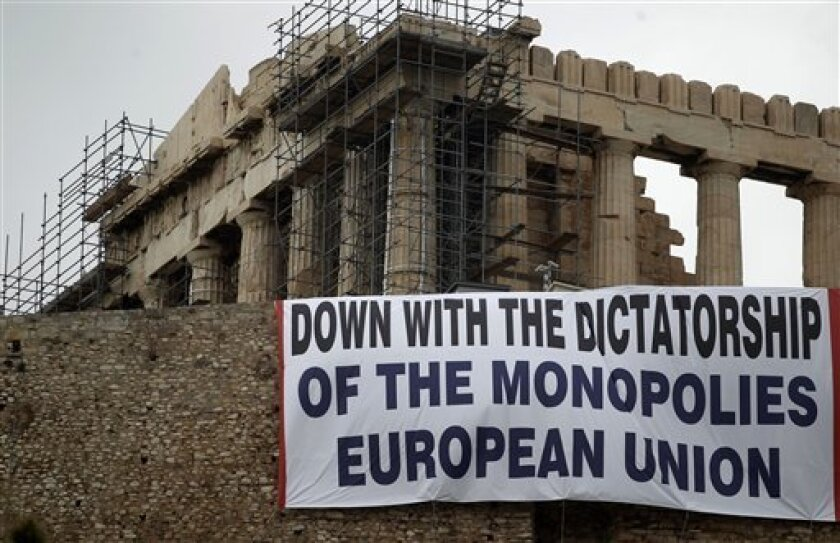 Greek communist party banner denounces EU policies under the temple of Parthenon at the Athen's Acropolis hill on Saturday Feb. 11, 2012. Lawmakers from two parties backing Greece's coalition government are meeting Saturday to consider support for legislation containing new austerity measures, which Socialist leader George Papandreou has urged his deputies to back, saying the country faces disaster if the new bailout deal falls through. (AP Photo/Petros Giannakouris)