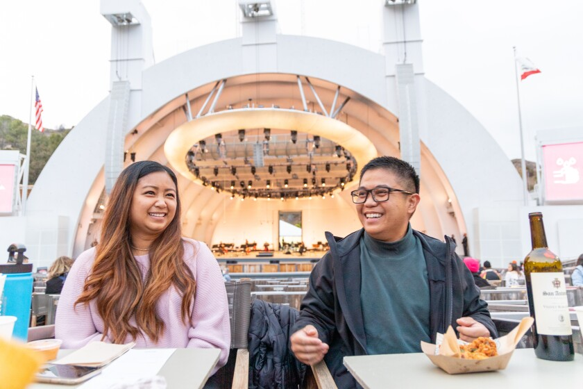 KC Cortez  and husband Allen Cortez sit in Hollywood Bowl box seats before the concert, with the empty stage behind them.