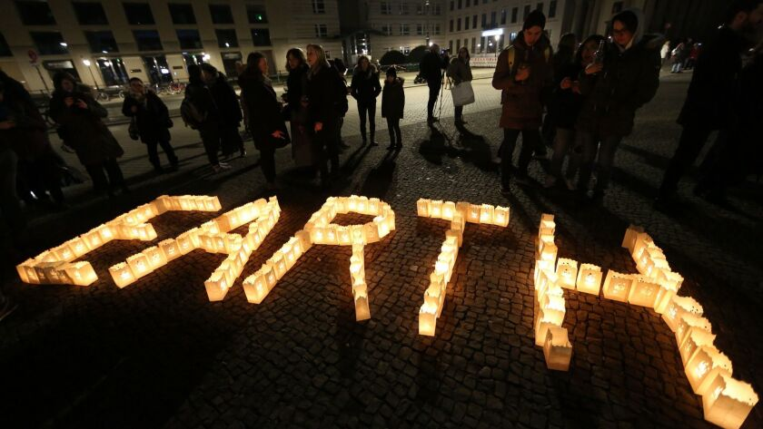Participants take part in Earth Hour 2018 in front of Berlin's Brandenburg Gate on Saturday. Organizers say Earth Hour has participants in 154 countries and territories and over 5,000 cities agreeing to switch off their lights for one hour.