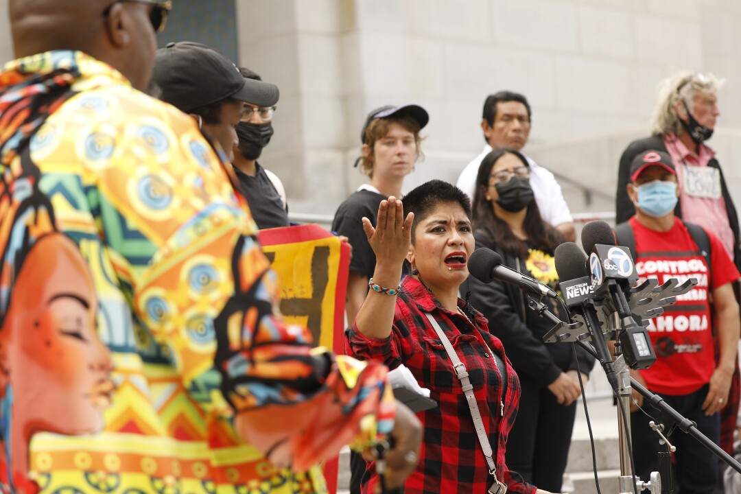 A woman, surrounded by other people, speaks into news microphones