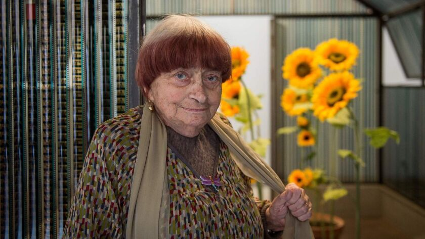 "Agnès Varda poses next to her art installation ""La Serre du Bonheur."""