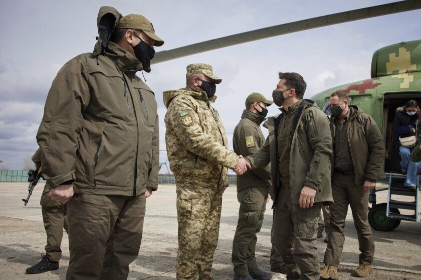Ukrainian President Volodymyr Zelenskiy shakes hands a soldier as he visits the war-hit Donetsk region, eastern Ukraine, Thursday, April 8, 2021. Ukraine is at the center of a major geopolitical battle in the eastern part of the country with Moscow backed separatists. (Ukrainian Presidential Press Office via AP)