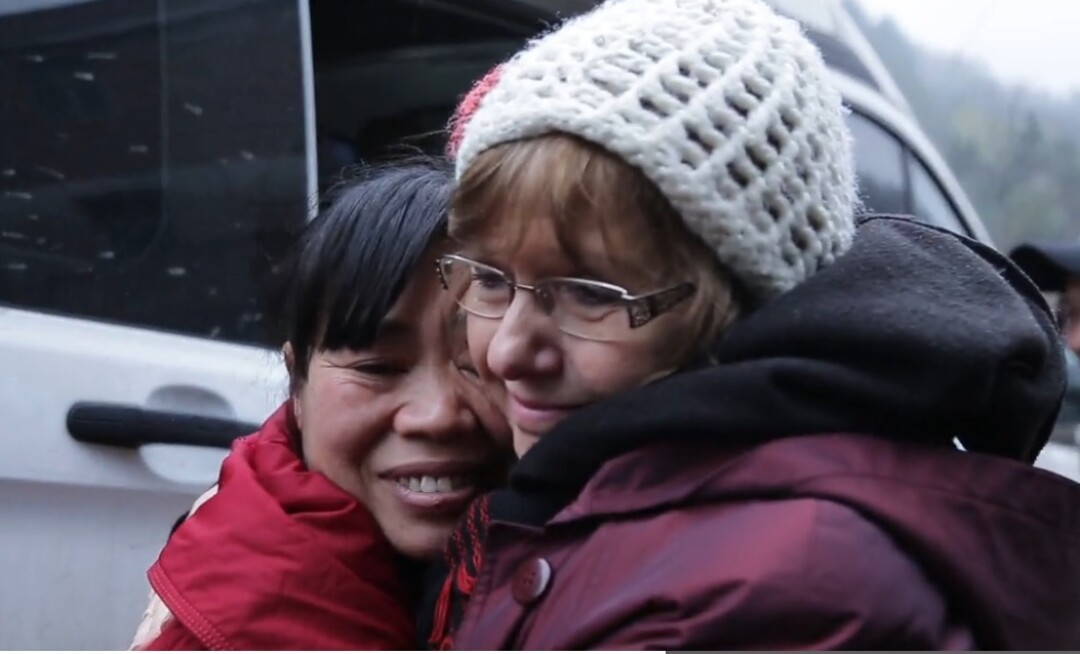 Yuan Zanhua, the twins' birth mother, and Marsha Frederick, Esther's adoptive mother, embrace during the reunion.