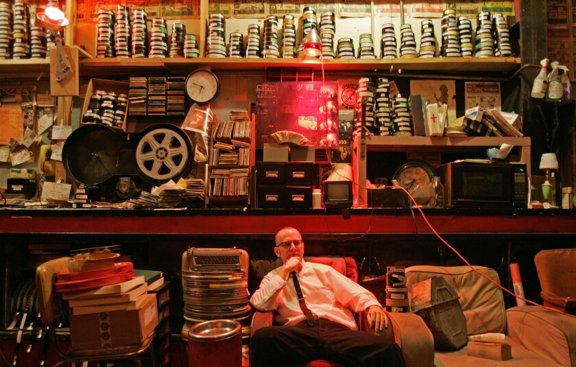 Brian Quinn, a manager at the New Beverly, sits in the movie house's projection room surrounded by o