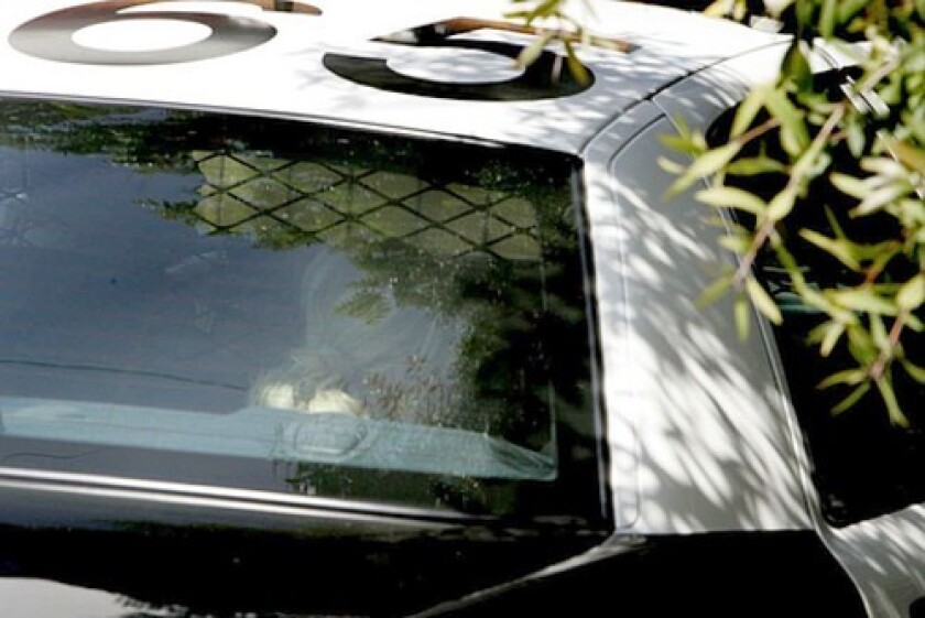 Paris Hilton leaves her home in the back of a L.A. Sheriff's squad car. She was ordered by a judge to return to jail.