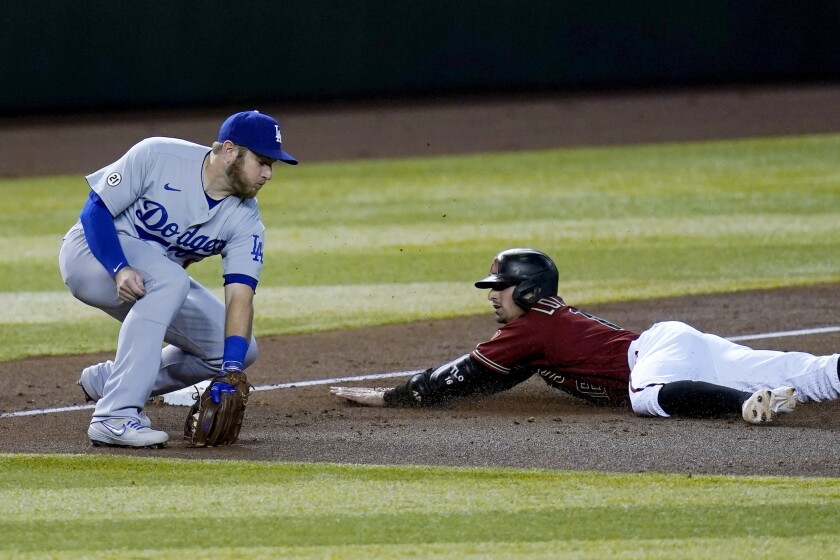 Arizona Diamondbacks' Tim Locastro slides safely into third base with an RBI triple as Los Angeles Dodgers third baseman Max Muncy makes a catch on a late throw during the second inning of a baseball game Wednesday, Sept. 9, 2020, in Phoenix. (AP Photo/Ross D. Franklin)