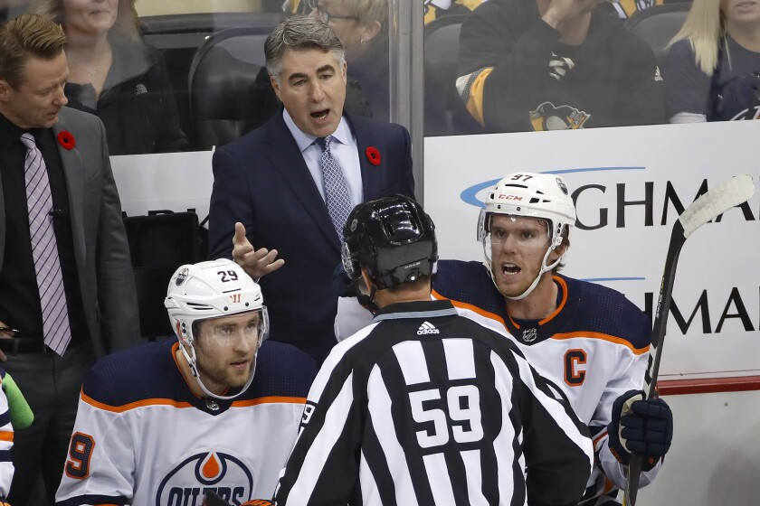Oilers coach Dave Tippett stands behind Connor McDavid (97) and Leon Draisaitl (29) as he talks with linesman Steve Barton (59) during a game Nov. 2.