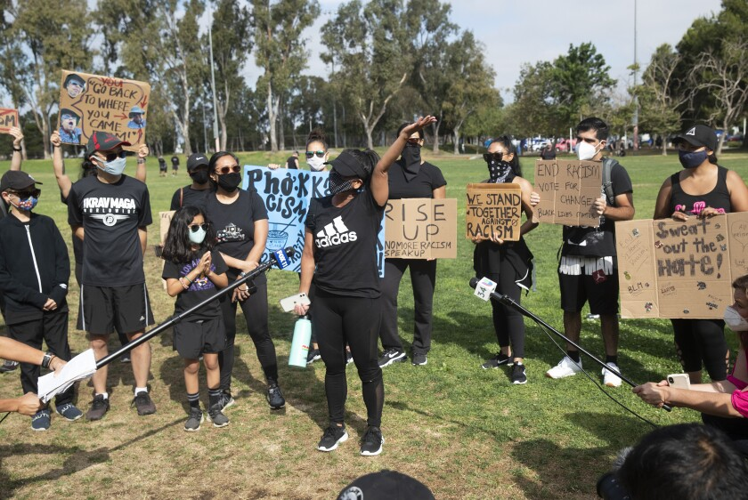 """People dressed in black listen at the conclusion of the """"We Sweat With You"""" rally and workout at Wilson Park in Torrance"""